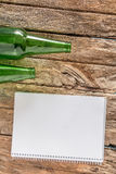 Old paper is placed on the table with a bottle of empty wine pla. Ced together stock photo