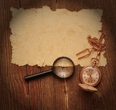 Old paper with pocket watch and magnifying glass Stock Photos