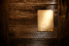 Old Paper Poster Board on Aged Antique Wood Wall. Old blank parchment paper western poster board notice with empty copy space display on aged and weathered barn Stock Photos