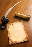 Old paper, quill pen and scroll on wooden table Royalty Free Stock Image
