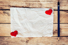 Old paper and red heart with pencil on wood background for valen Royalty Free Stock Images