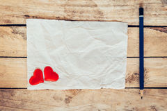 Old paper and red heart with pencil on wood background for valen Stock Photography