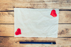 Old paper and red heart with pencil on wood background for valen Stock Photos