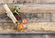 Old paper roll and dry rose on a wooden background. Old paper roll and dry rose on wooden background. Top view stock image