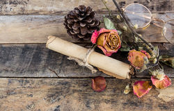 Old paper roll, glasses,and dry rose on wooden Stock Images