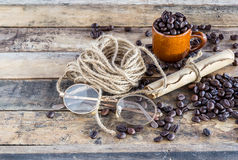 Old paper roll, glasses, rope reel and coffee beans on wooden Royalty Free Stock Photography