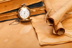 Old paper rolls. In foreground, vintage pocket watch and books on blurred background royalty free stock image