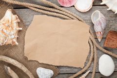Old paper with rope and seashells on wooden textured background Stock Photo