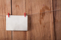 Old paper on rope on wood background. Place for text Royalty Free Stock Photo