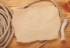 Old paper and rope on wooden textured background Royalty Free Stock Images
