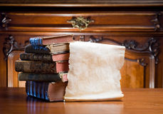 Old paper scroll with antique books. Old worn paper scroll with copy space next to antique books stock photo