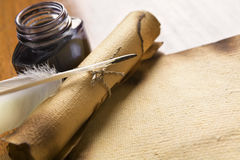 Old paper, scroll and quill on wooden table Royalty Free Stock Images