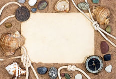Old paper, sea shells and rope. On sand background Stock Photography