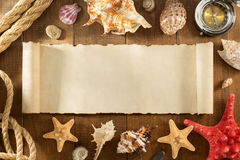 Old paper and seashell on wooden background Royalty Free Stock Images