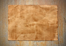 Old paper sheet on old wood background texture.  Royalty Free Stock Image