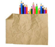 Old paper sheet and stack of colored pencils. On white background Royalty Free Stock Image