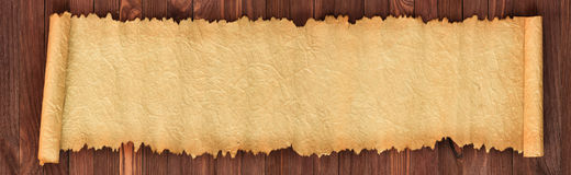 Old paper on the table, panorama in high resolution. Open ancient scroll on a wooden table, panoramic paper background stock photography
