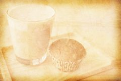 Old paper texture with a cup of coffee and a muffin. Vintage paper texture with a glass of cappuccino and a muffin Royalty Free Stock Photography