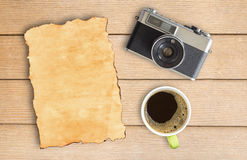 Old paper and vintage camera with coffee cup on wood table. Top view with copy space Royalty Free Stock Photography