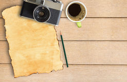 Old paper and vintage camera with coffee cup on wood table. Top view with copy space Royalty Free Stock Images