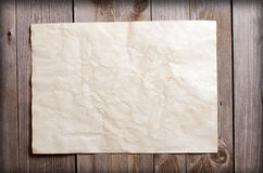Old paper on a wooden surface Royalty Free Stock Images