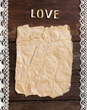 Old paper and word  Love on the wood background Royalty Free Stock Photography