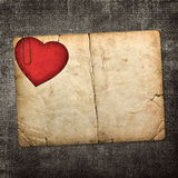 Old paperboard card with red paper heart on a dark fabric backgr. Ound Royalty Free Stock Images