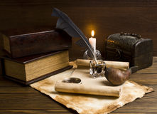 Old papers and books on a wooden table. Old articles, compass, book and candle on wooden table Stock Photo