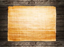 Old papyrus paper. On wooden background Royalty Free Stock Image