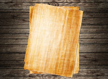 Old papyrus paper. On wooden background Royalty Free Stock Photos