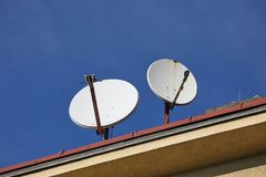 Old Parabola Receivers. Parabola satellite receivers on a roof, pointed at the sky Royalty Free Stock Image