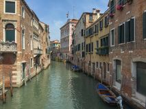 Old and parallel buildings between a canal in Venice, Italy. Perspective of one of the canals of Venice, with its typical houses and boats Royalty Free Stock Photos
