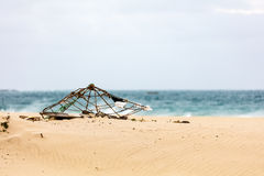 Old parasol on a beach. Old, partially decomposed parasol on a sand beach Royalty Free Stock Images