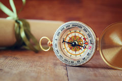 Old parchment and antique compass on wooden table Royalty Free Stock Photos