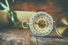 Old parchment and antique compass on wooden table Royalty Free Stock Image
