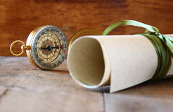 Old parchment and antique compass on wooden table Royalty Free Stock Images