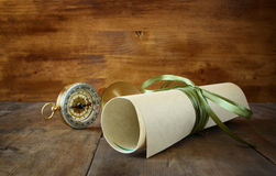 Old parchment and antique compass on wooden table Royalty Free Stock Photography