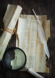 Old parchment, magnifier and quill pen Royalty Free Stock Photography