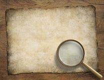 Old parchment or map on wooden desk with Royalty Free Stock Photography