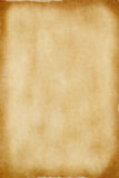 Old Parchment Paper. A sheet of yellowed. patchy parchment paper with darker, aged brown torn edges for background texture and copy space Stock Images