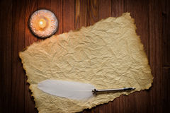 Old parchment paper with a quill and candle, Medieval theme with Stock Photos