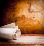 Ancient Scroll. Old ancient paper parchment scroll rolled up with a vintage background with copy space Stock Image