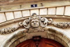 Paris building façade sculpture woman`s head front entrance. An old parisian building façade with a front door decorated with a a woman`s head in bas-relief royalty free stock photo