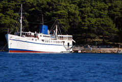 Old passanger ship docked in Mali Losinj,Croatia. Passanger ship Marina docked in bay in Mali Losinj at the adriatic sea with pine tree forest in background Stock Photography