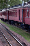 Old Passenger Cars. Old red passenger cars on side track with active rails in front stock photo