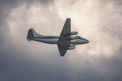 Old passenger plane on cloudy sky Stock Image