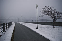 Old path in the Fog. A riverside path in the fog in winter, sidelined by old street lamps Stock Image