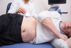 Old patient having ultrasonic scanning of abdomen in the clinic Stock Photography