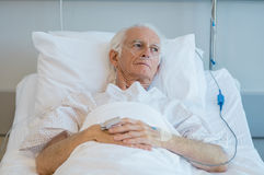 Old patient lying on bed. Senior man with oxygen tube lying on hospital bed. Sad old patient feeling sick at hospital. Depressed old man hospitalized in a Stock Images