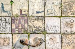 Old patterned tiles with abstract pictures. Topics and footprint Royalty Free Stock Photo
